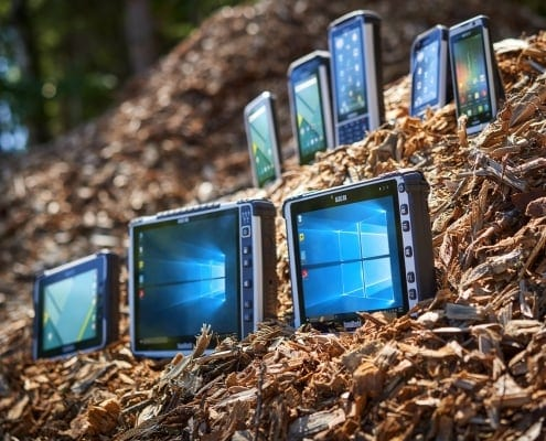 handheld rugged tablets in pile of wood chips