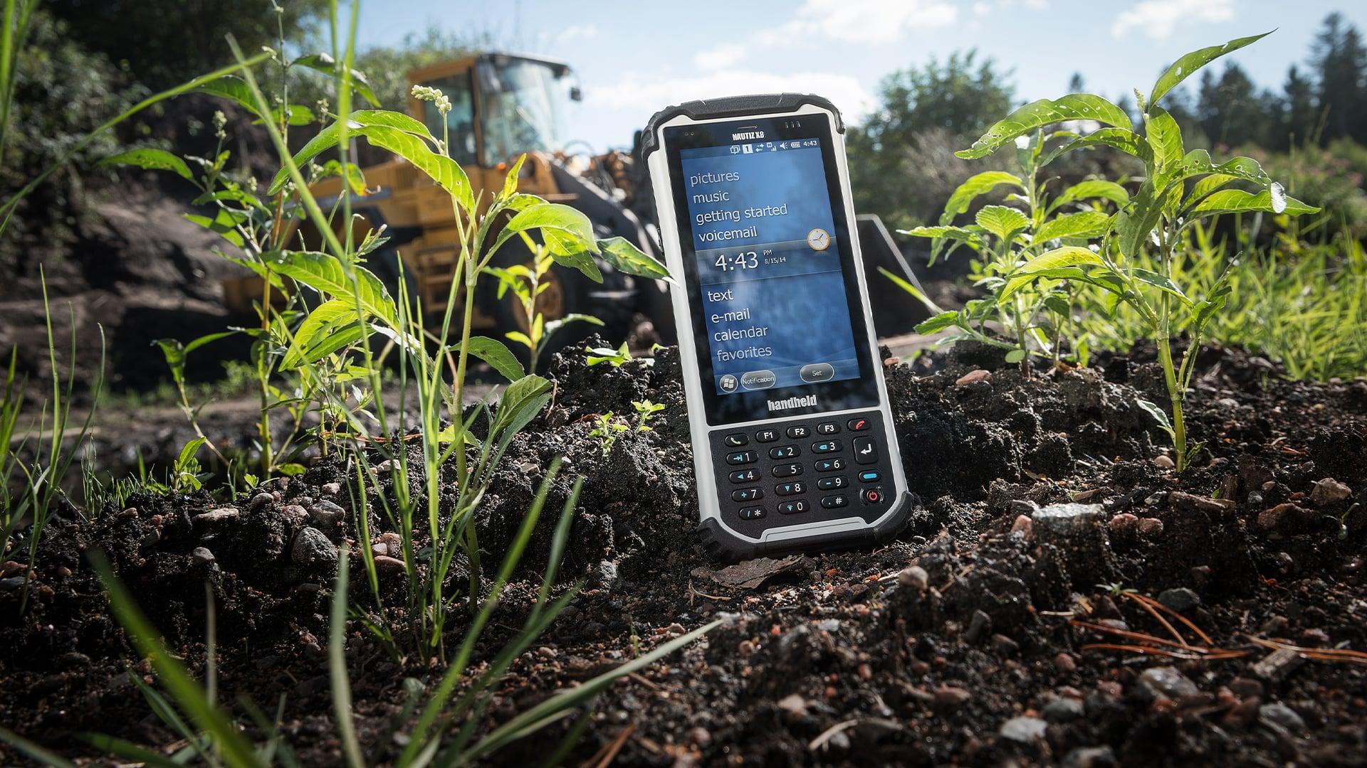 handheld nautiz x8 on ground next to plants
